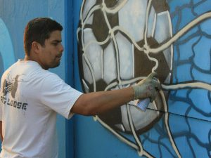 "Leonardo Dogh applies his art to the mural. ""Projeto 4km represents an opportunity to show our work, get a good commission and gain visibility with pieces that are 100% the work of each artist,"" he said. (Thiago Borges for Infosurhoy.com)"
